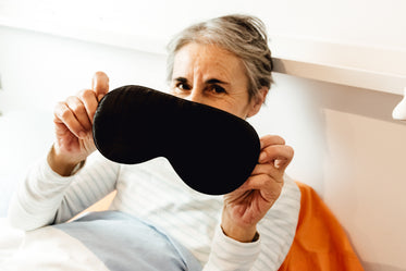 person in bed holds their eye mask for the camera
