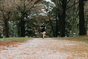 person in black face mask running on dirt path