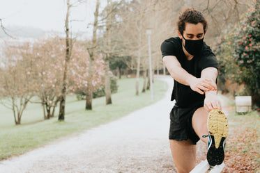 person in black face mask stretches for a run