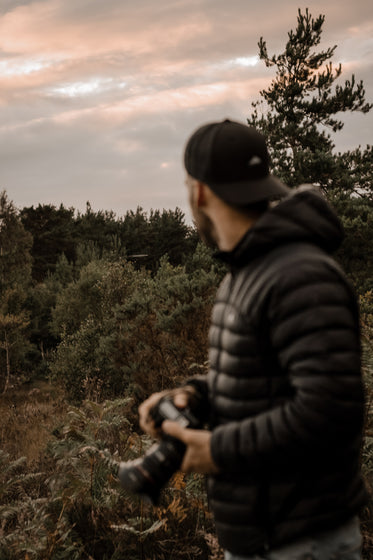 person in black holding a camera with the forest behind