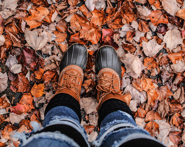 person in boots stand on crunchy fall leaves