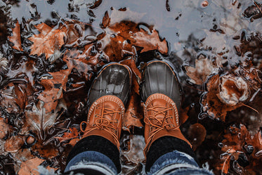 person in boots standing in leaves and water