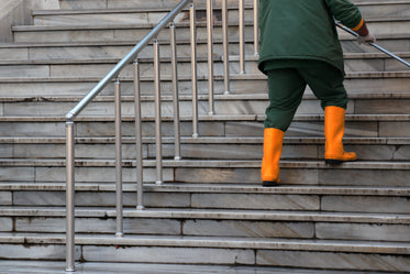 person in green and orange walk up white stone steps