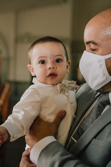 person in grey suit and facemask holds a young baby