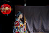 person in kimono peaks behind a black curtain