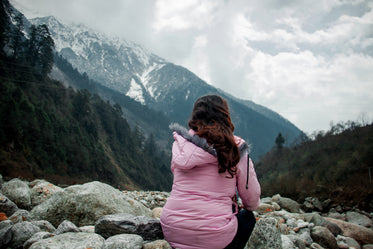 person in pink looks out to a mountain view