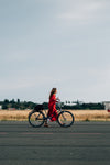 person in red dress walks bicycle down the road