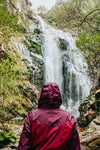 person in red raincoat admires a huge waterfall