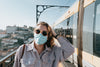 person in sunglasses and a facemask stands by a train
