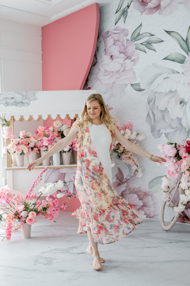 person in white dances in a floral room