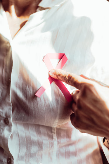 person in white holding a pink ribbon to their chest