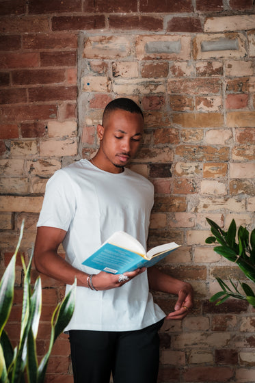person in white stands reading a novel by a brick wall