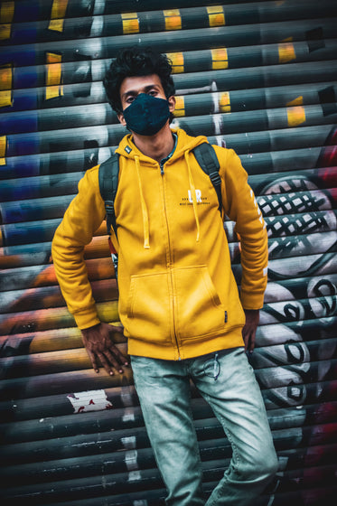 person in yellow leans against graffiti covered wall