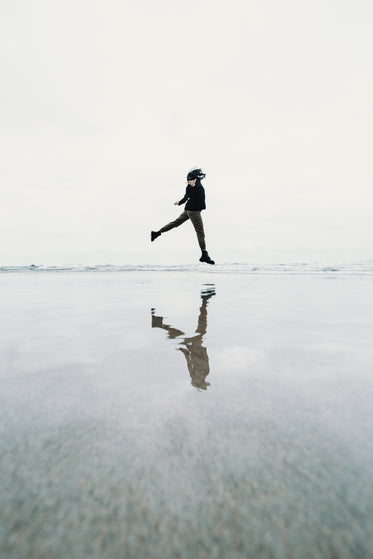 person jumping on beach creating a floating illusion