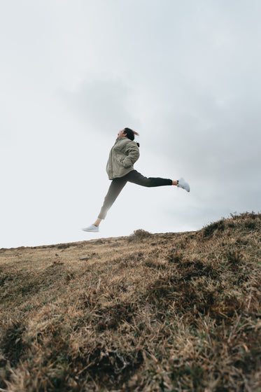 person jumps high with legs out above a brown grassy hill
