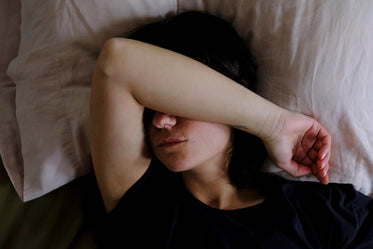 person lays down with one arm up to cover their eyes