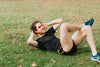 person lays on grass and crunches in a situp