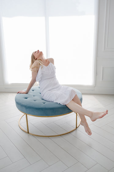 person leans back relaxing on a blue couch