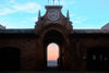 person leans on archway wall and takes in the sunset