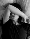 person lying with their arm up in bed in black and white