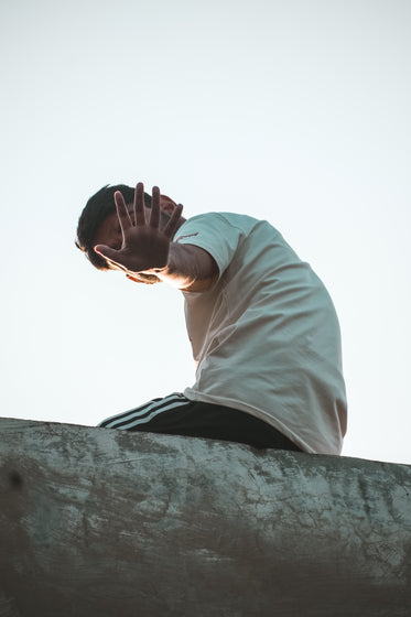 person on a ledge hand up to hide their face