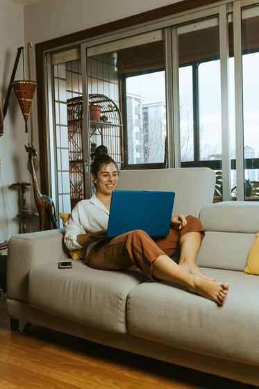 person on couch smiles at laptop screen