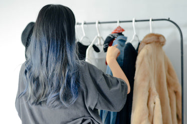 person organizes clothes on a thin clothing rack