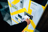 person places cash into a yellow and white machine