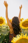 person reaching while standing in a sunflower field