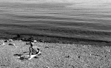 person resting on their beach towel in black and white