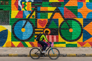 person rides a bike with a mural of a bike behind them