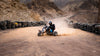 person rides a vehicle leaving a cloud of sand behind
