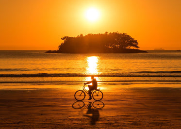 person riding their bike at sunset along the beach