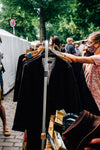 person shops for clothes in an outdoor market