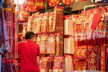 person shops in a store selling red and gold decorations