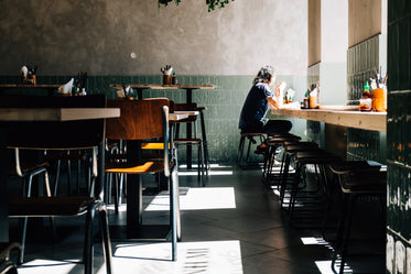 person sits alone by the window of a quiet restaurant