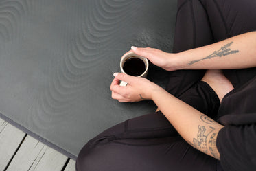 person sits cupping a mug with both hands
