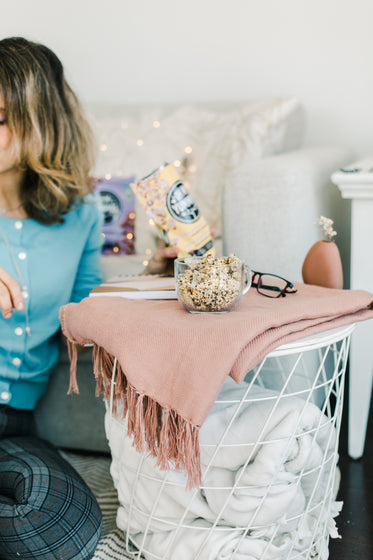person sits in living room around blankets with snacks
