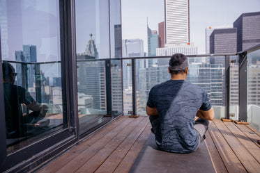 person sits on a grey yoga mat on a wooden deck