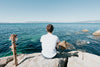 person sits on a rock and looks out to the water