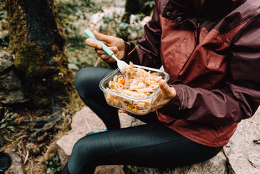 person sits on a rock outdoors and eats pasta salad