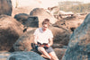 person sits on rocks and reads a novel in white shirt