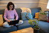 person sits on there couch working on there laptop