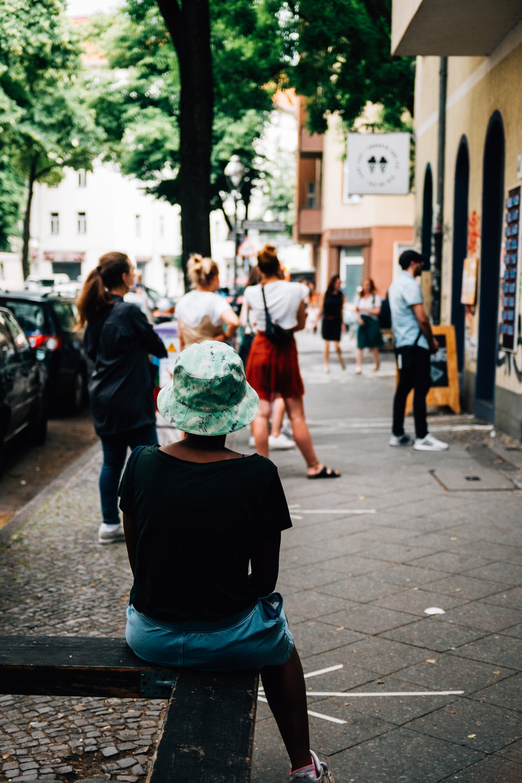 Person Sits Waiting In Line Outside A Shop