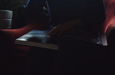 person sits with a large book in their lap in the dark
