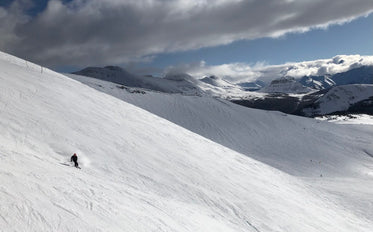 person skiing down the snow covered mountain