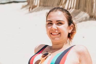person smiles while laying back on the beach