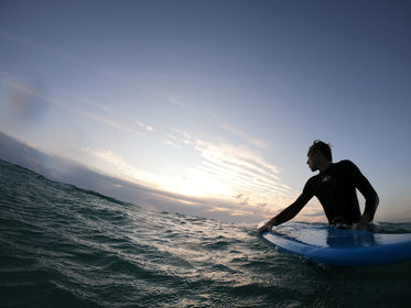 person standing in wavy water holding a surfboard