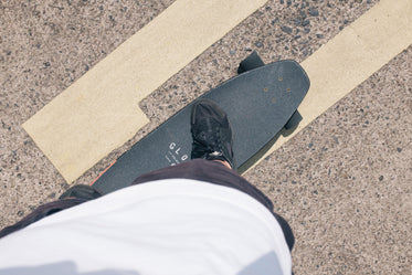 person standing on a black skateboard on a paved road