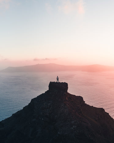 person standing on a far cliff taking a the setting sun